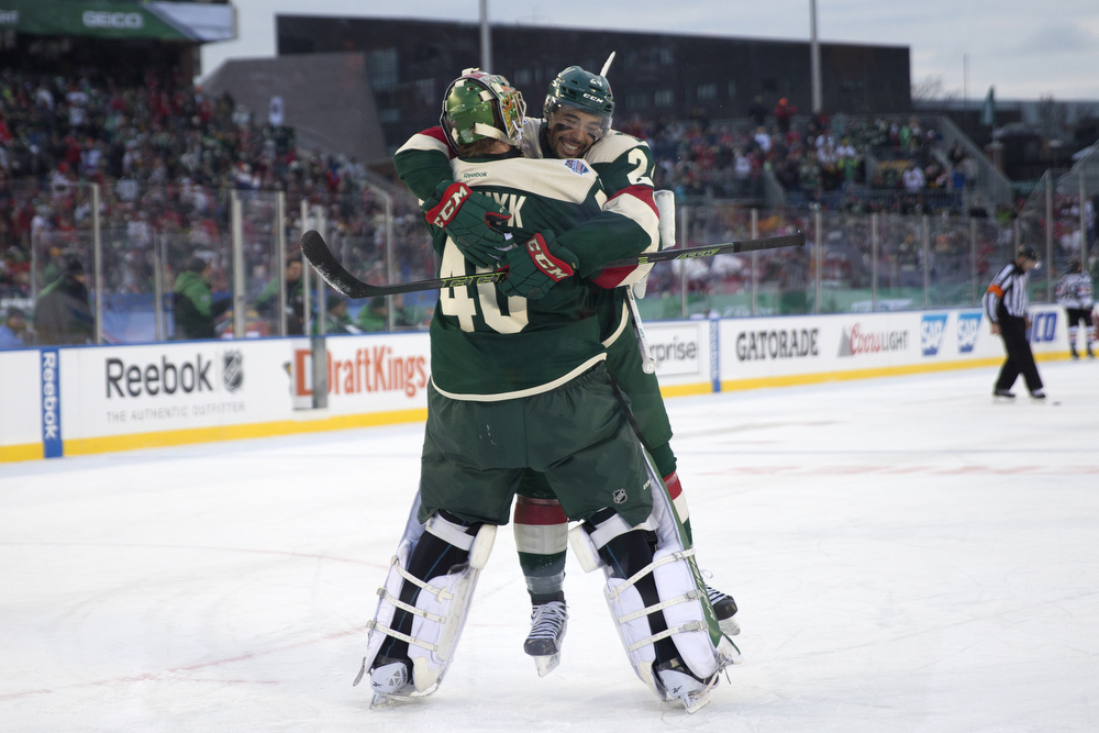 Minnesota Wild defenseman Matt Dumba (24) jumps into the arms of Minnesota Wild goalie Devan Dubnyk (40) after the third period of the Chicago Blackhawks versus Minnesota Wild 2016 NHL Stadium Series outdoor game at TCF Bank Stadium on the University of Minnesota Campus Sunday, Feb. 21, 2016, in Minneapolis. The Wild beat the Blackhawks 6-1. (Erin Hooley/Chicago Tribune)