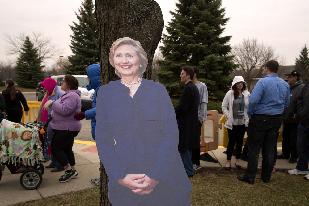 A cardboard cutout of Democratic presidential candidate Hillary Clinton leans against a tree as hundreds of people wait in line to see her speak at the Sullivan Community Center Thursday, March 10, 2016, in Vernon Hills, Ill. The Illinois state primary is March 15.  (Erin Hooley/Chicago Tribune)