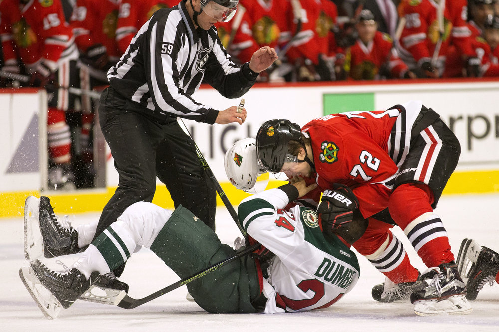 The helmet of Minnesota Wild defenseman Matt Dumba (24) flies off as he's taken down by Chicago Blackhawks left wing Artemi Panarin (72) during the third period of the Minnesota Wild versus Chicago Blackhawks game at the United Center Sunday, March 20, 2016, in Chicago. Panarin received a two-minute roughing penalty. (Erin Hooley/Chicago Tribune)