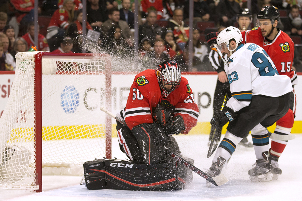 Chicago Blackhawks goalie Corey Crawford (50) gets an ice shower from San Jose Sharks left wing Matt Nieto (83) as he makes a save during the second period of the Chicago Blackhawks versus the San Jose Sharks game at the United Center Tuesday, Feb. 9, 2016, in Chicago. The Sharks lead 1-0 at the end of the second. (Erin Hooley/Chicago Tribune)