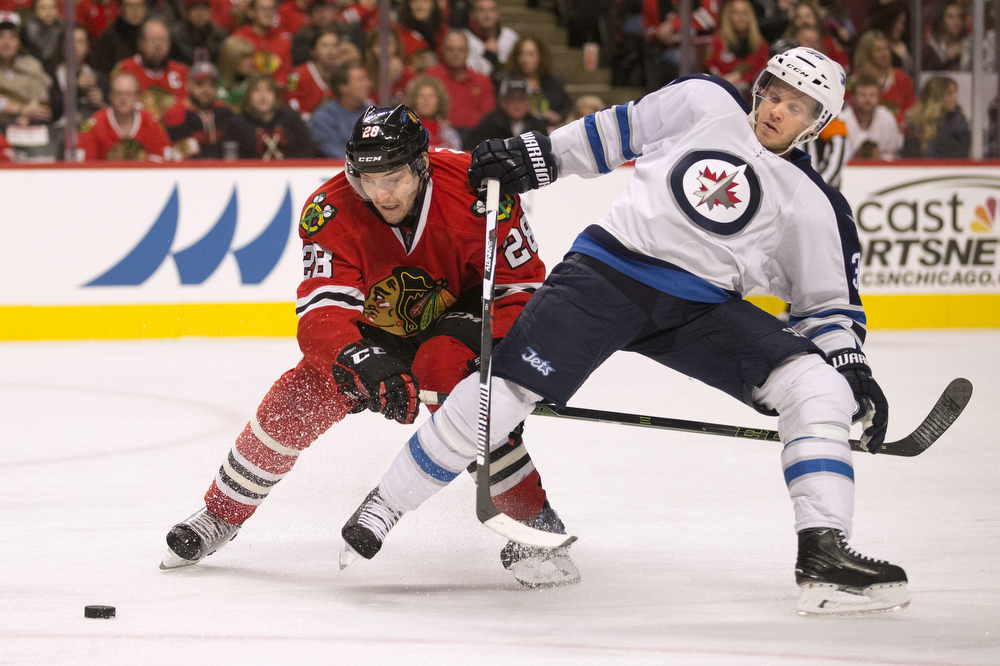 Winnipeg Jets defenseman Tobias Enstrom (39), right, gets tangled with Chicago Blackhawks left wing Ryan Garbutt (28) during the third period of the game at the United Center Sunday, Dec. 6, 2015 in Chicago. (Erin Hooley/Chicago Tribune)