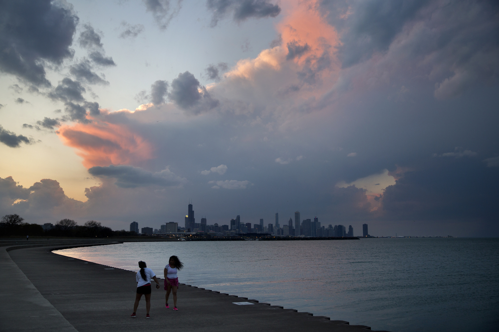 People walk along the lakefront near the Oakwood/41st Street Beach as storm clouds roll over downtown Chicago Monday, April 25, 2016. The National Weather Service issued a severe thunderstorm watch in north central and north eastern Illinois valid until 10 p.m. (Erin Hooley/Chicago Tribune)