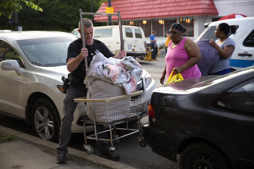 A member of the Chicago Police Department helps a woman move her laundry around the scene of a fatal shooting in the 2900 block of West Armitage Avenue in Logan Square Friday, June 3, 2016, in Chicago. A 20-year-old man was shot and pronounced dead at the scene and a 21-year-old man was shot in the right leg and was taken to Advocate Illinois Masonic Hospital. (Erin Hooley/Chicago Tribune)