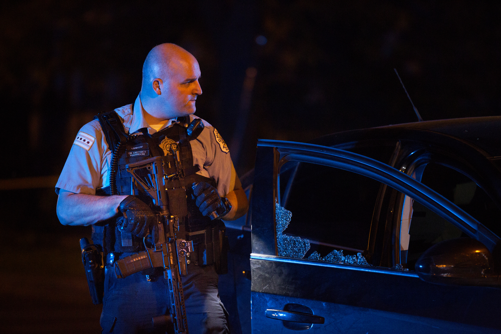 A member of the Chicago Police Department carries a weapon as he inspects a vehicle involved in a shooting in the 500 block of North Springfield Avenue Saturday, June 4, 2016, in the East Garfield Park neighborhood in Chicago. A 20-year-old man went to Stroger Hospital with gunshot wounds to the leg. (Erin Hooley/Chicago Tribune)