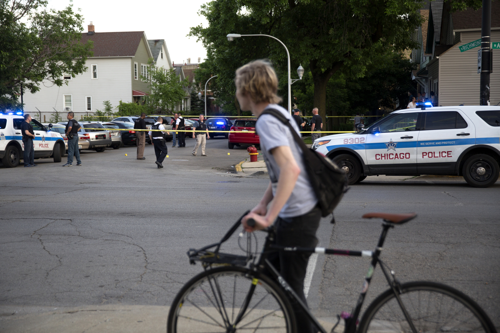 A bicyclist passes by as members of the Chicago Police Department work the scene of a fatal shooting in the 2900 block of West Armitage Avenue in Logan Square Friday, June 3, 2016, in Chicago. A 20-year-old man was shot and pronounced dead at the scene and a 21-year-old man was shot in the right leg and was taken to Advocate Illinois Masonic Hospital. (Erin Hooley/Chicago Tribune)