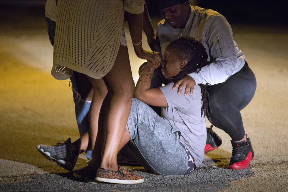 Several women comfort a woman on the ground outside of Advocate Trinity Hospital Wednesday, June 1, 2016, in Chicago. 15-year-old Fabien Lavinder was shot in a vehicle in the 2900 block of East 89th Street late Tuesday and later died at the hospital. (Erin Hooley/Chicago Tribune)