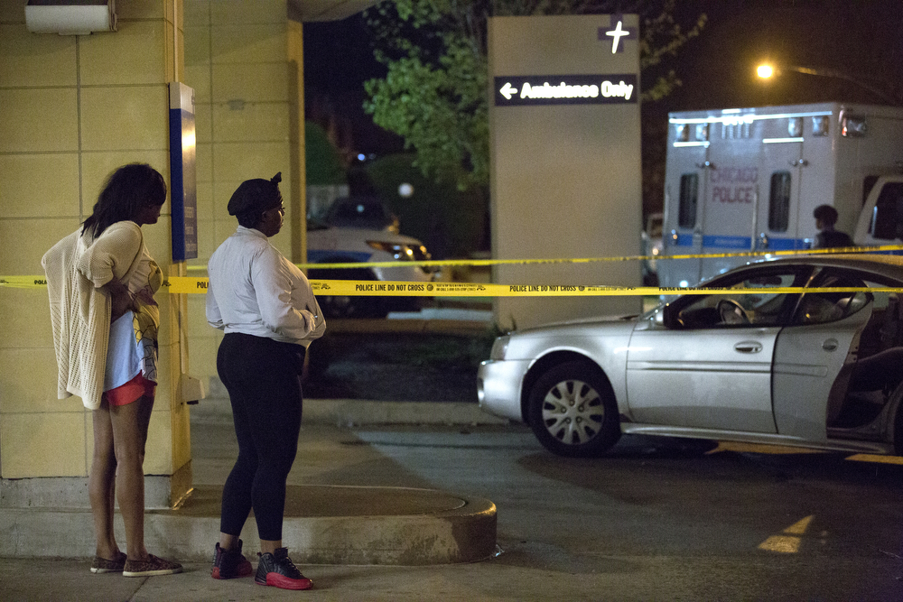 Two women waiting outside the emergency room of Advocate Trinity Hospital look at a vehicle taped off by Chicago Police Wednesday, June 1, 2016, in Chicago. 15-year-old Fabien Lavinder was shot in the vehicle in the 2900 block of East 89th Street late Tuesday and later died at the hospital. (Erin Hooley/Chicago Tribune)