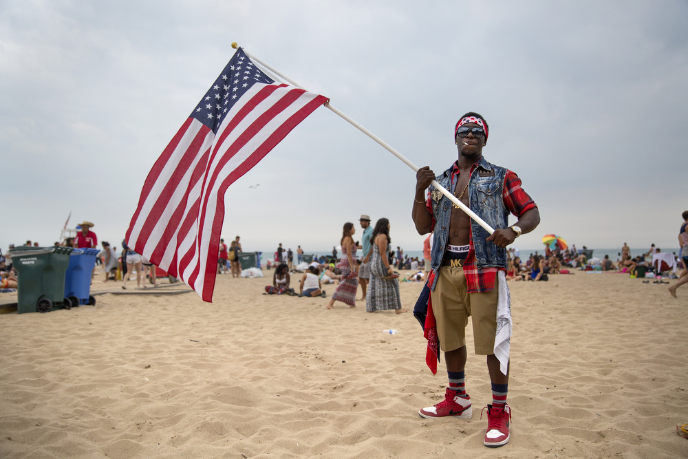 Vernon Mems carries an American Flag at North Avenue Beach Monday, July 4, 2016, in Chicago. (Erin Hooley/Chicago Tribune)