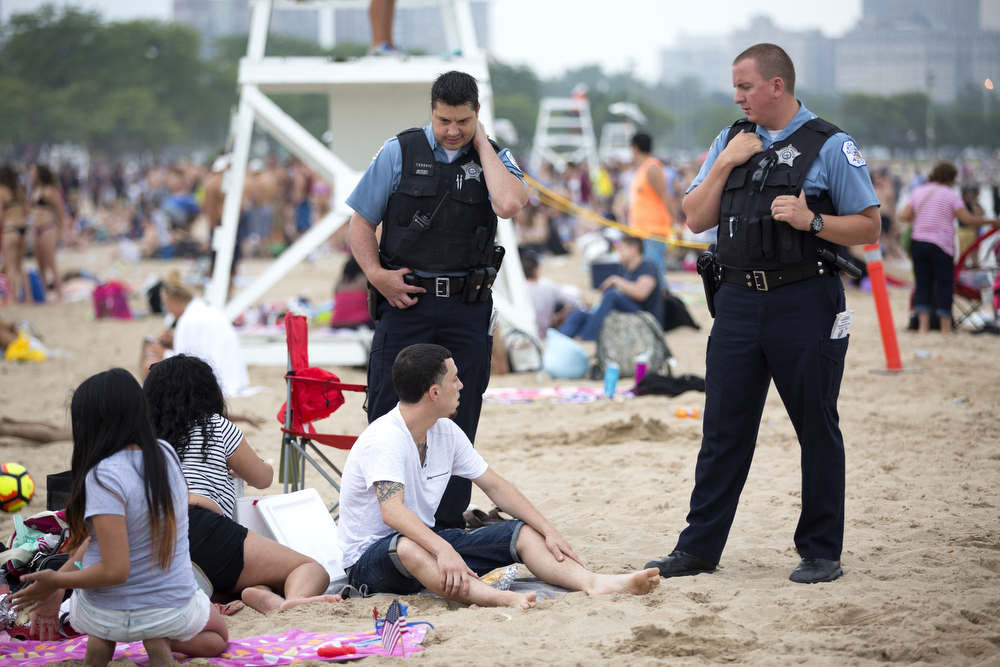 Members of the Chicago Police Department talk to beachgoers at North Avenue Beach Monday, July 4, 2016, in Chicago. (Erin Hooley/Chicago Tribune)