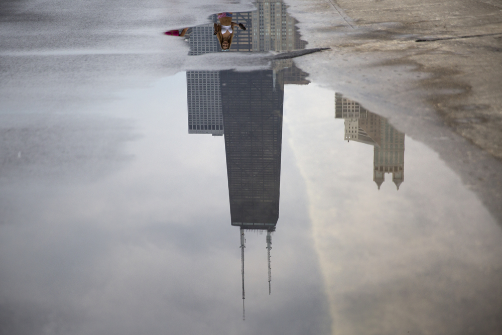 The John Hancock Center is reflected in water along the Lakefront Trail near Oak Street Beach Monday, July 4, 2016, in Chicago. (Erin Hooley/Chicago Tribune)