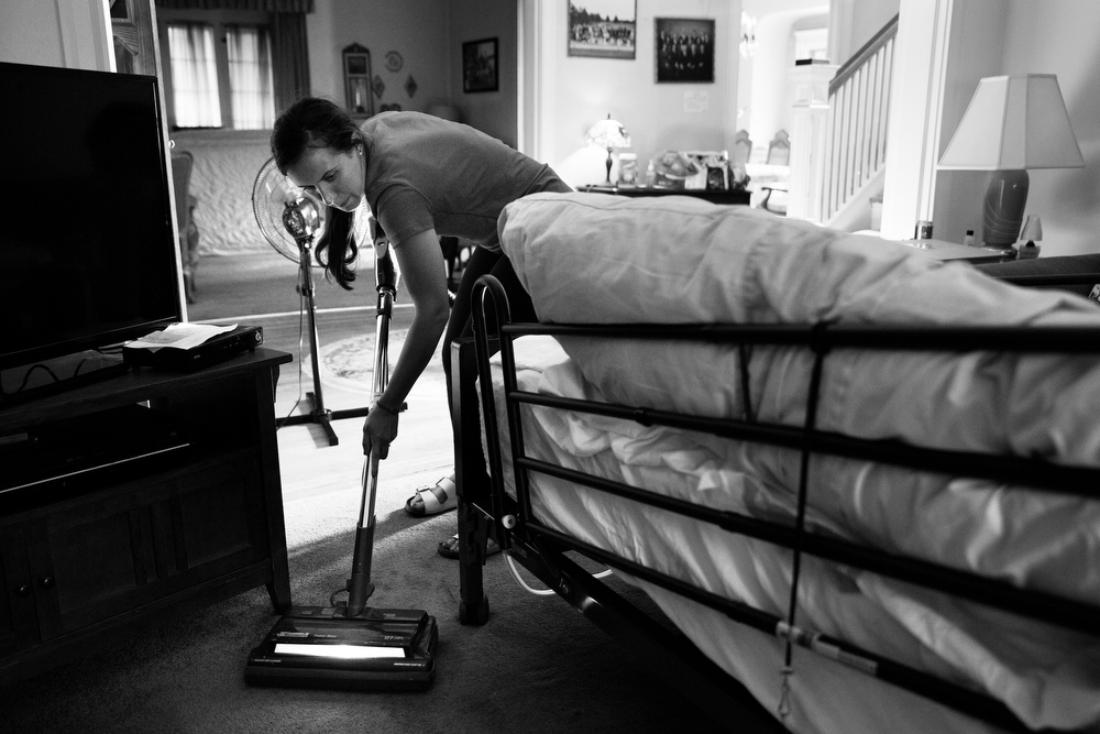 Molly Morris, 21, one of 92-year-old Margaret Coleman's 48 grandchildren, vacuums around her bed during a visit at the Coleman family home Monday, July 25, 2016, in Chicago. Although she is on oxygen and can no longer walk, Margaret remains in high spirits and wishes to stay in the family house, so her children organize and take turns caring for her during the week. She also receives frequent visits from many of her 48 grandchildren and 13 great-grandchildren. (Erin Hooley/Chicago Tribune)