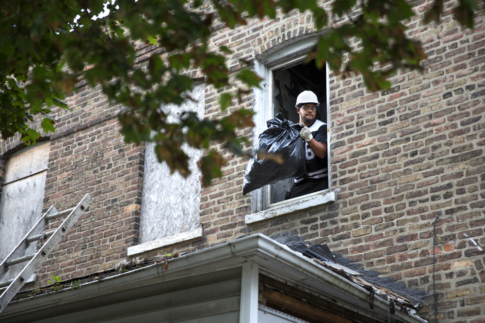 David Johnson throws a bag of debris out the window of a house he is helping to renovate Wednesday, Oct. 12, 2016, in the Pullman neighborhood of Chicago. About 28 young men are participating in a pilot program launched by the Emerson Collective meant to help them learn job skills and find future employment while participating community renewal in many Chicago neighborhoods.  (Erin Hooley/Chicago Tribune)