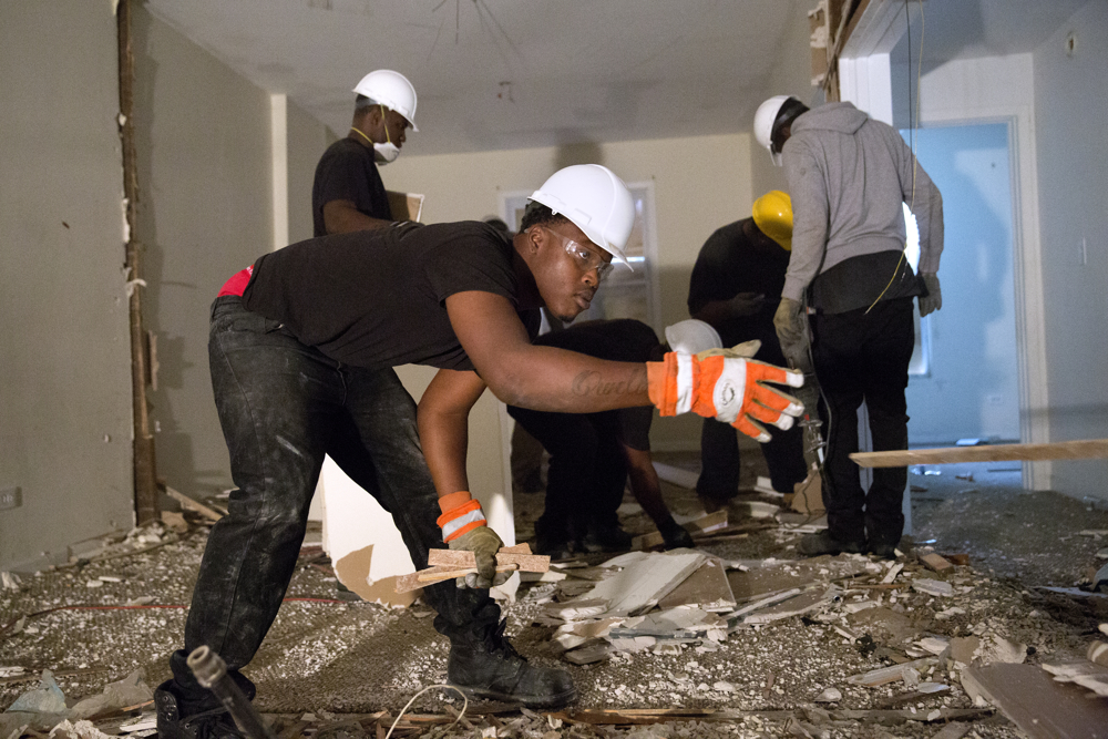 Antonio Jones tosses a piece of wood as he and others deconstruct a house Wednesday, Oct. 12, 2016, in the Pullman neighborhood of Chicago. About 28 young men are participating in a pilot program launched by the Emerson Collective meant to help them learn job skills and find future employment while participating community renewal in many Chicago neighborhoods.  (Erin Hooley/Chicago Tribune)