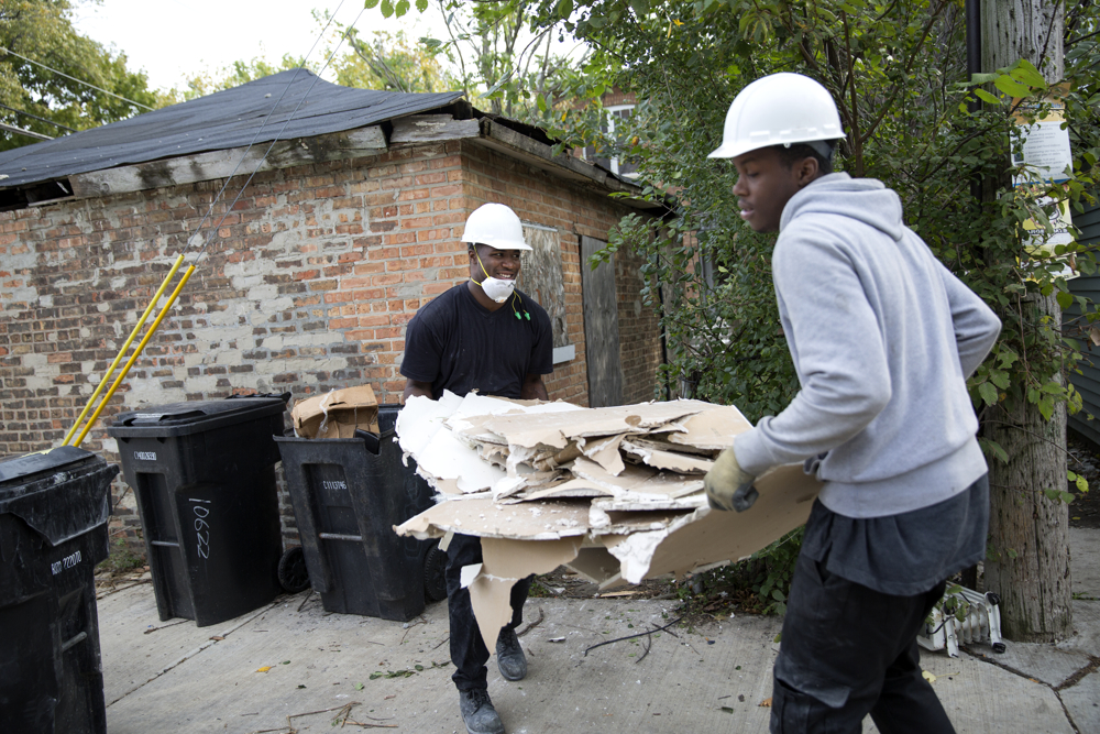 Kaysean Thomas, left, and Jamon Lynch carry drywall from a house they are renovating Wednesday, Oct. 12, 2016, in the Pullman neighborhood of Chicago. About 28 young men are participating in a pilot program launched by the Emerson Collective meant to help them learn job skills and find future employment while participating community renewal in many Chicago neighborhoods.  (Erin Hooley/Chicago Tribune)