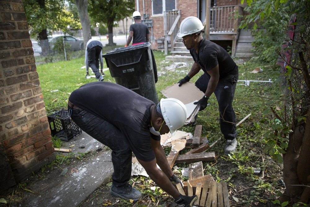 Kaysean Thomas, left, and Dwayne Williams pick up debris in the yard of a house they are renovating Wednesday, Oct. 12, 2016, in the Pullman neighborhood of Chicago. About 28 young men are participating in a pilot program launched by the Emerson Collective meant to help them learn job skills and find future employment while participating community renewal in many Chicago neighborhoods.  (Erin Hooley/Chicago Tribune)