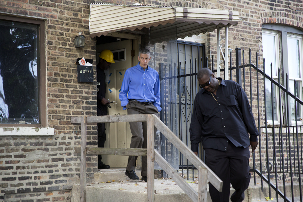 Former U.S. Secretary of Education and Chicago Public Schools chief Arne Duncan, left, tours a house under renovation with contractor Mike Wilson, right, Wednesday, Oct. 12, 2016, in the Pullman neighborhood of Chicago. About 28 young men are participating in a pilot program launched by the Emerson Collective, where Duncan is a managing partner, meant to help them learn job skills and find future employment while participating community renewal in many Chicago neighborhoods.  (Erin Hooley/Chicago Tribune)