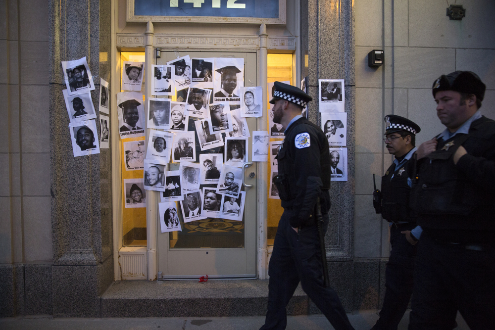 Three Chicago police officers walk by pictures demonstrators taped to the wall of Chicago police union headquarters Thursday, March 31, 2016, in Chicago. Demonstrators were protesting the hiring of Jason Van Dyke, the officer charged with first-degree murder in the shooting death of Laquan McDonald, as a janitor, and said the pictures were all of individuals that were shot by Chicago police officers. (Erin Hooley/Chicago Tribune)