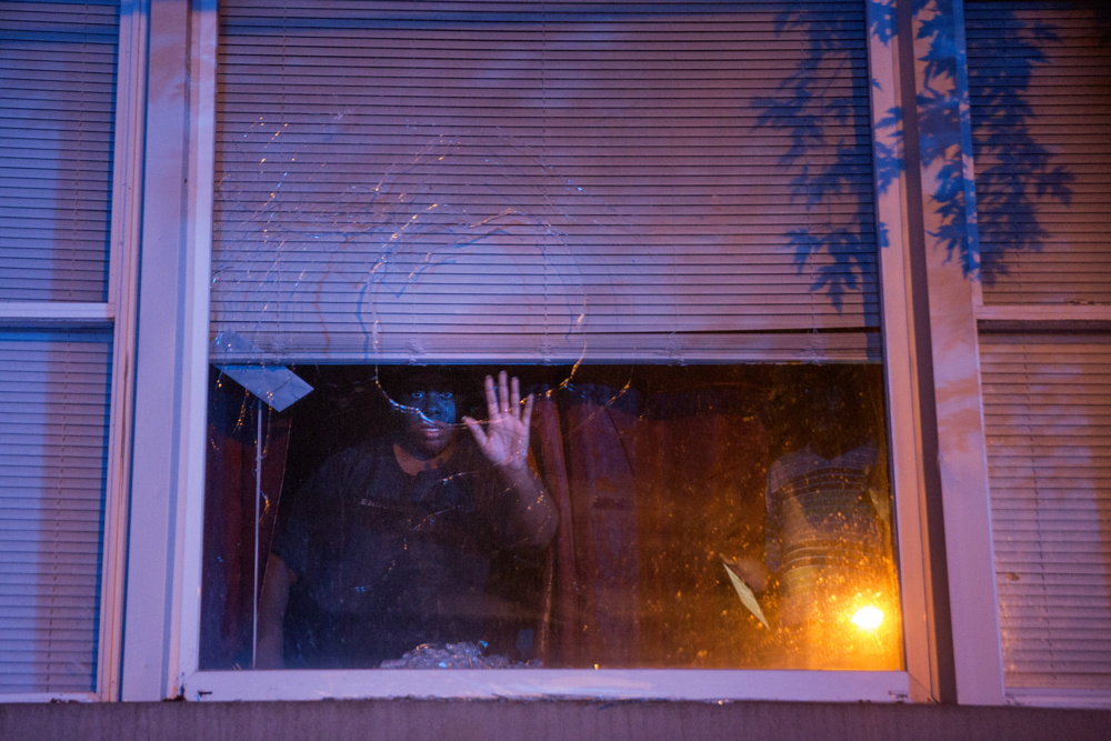 Chasity, who did not want to give her last name, looks out of the shattered window of her residence near the scene of a shooting in the 500 block of North Springfield Avenue Saturday, June 4, 2016, in the East Garfield Park neighborhood in Chicago. She said a bullet came through the glass but only shattered the outer pane of the two-pane window. A 20-year-old man went to Stroger Hospital with gunshot wounds to the leg. (Erin Hooley/Chicago Tribune)
