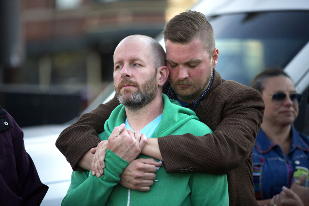 Joshua Oaks, right, puts his arms around his partner Mark Flannigan during a vigil for the victims of the Orlando gay nightclub shooting Sunday, June 12, 2016, in the Boystown neighborhood of Chicago. 49 people were killed and 53 others wounded when Omar Marteen opened fire in the crowded Pulse nightclub.  (Erin Hooley/Chicago Tribune)