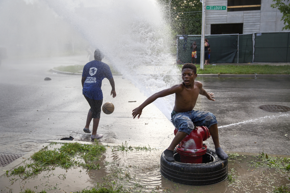 Children play in the water from a fire hydrant in the 600 block of North Saint Louis Avenue Thursday, July 21, 2016, in the East Garfield Park neighborhood of Chicago. (Erin Hooley/Chicago Tribune)