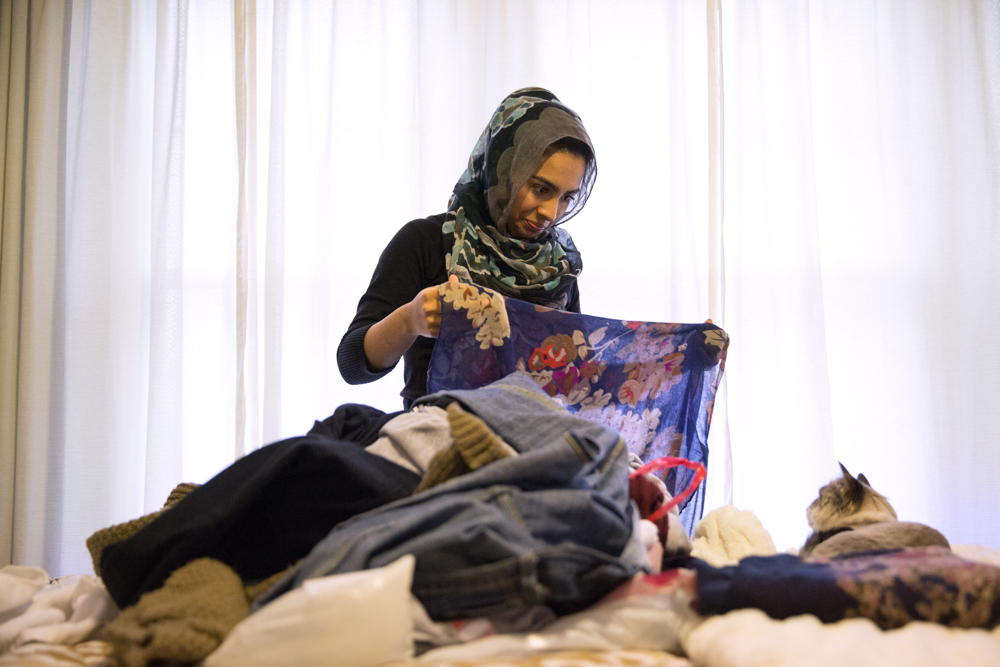 "Saarah Bhaiji, 16, who is Muslim, folds one of her many headscarves at her home Sunday, Jan. 31, 2016, in Glenview, Ill. Bhaiji teaches at the Muslim Education Center in Morton Grove on Sundays and attends the public school Glenbrook South High as a junior during the week. Saarah was an infant at the time of the Sept. 11 attacks on the U.S. and her sister Aasiyah, 13, wasn't born, but both teenagers have grown up beneath a cloud of suspicion about their faith. Shortly after the Paris terrorist attacks in 2015 that killed 130 people, one of Saarah's teachers at Glenbrook stood up and spoke on her behalf. ""How could you think what's going on in Paris and what's going on with ISIS is representative of Islam if you have people like Saarah?"" he said. (Erin Hooley/Chicago Tribune)"