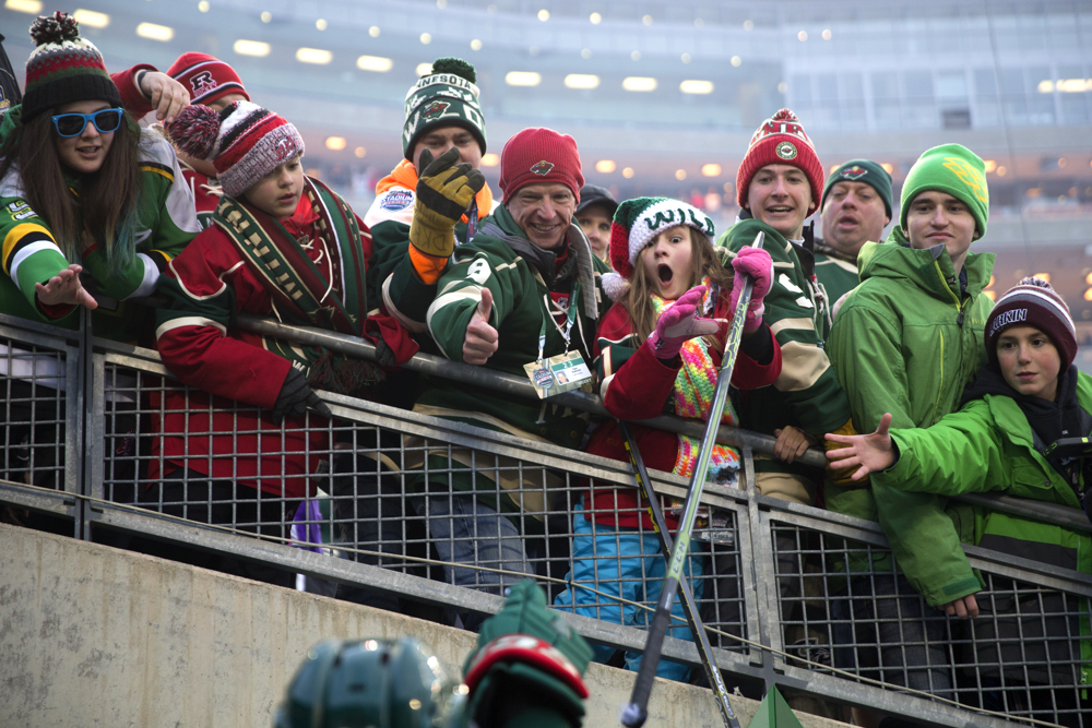 A young fan receives a stick from Minnesota Wild defenseman Matt Dumba (24) as the Minnesota Wild leave the ice after defeating the Chicago Blackhawks 6-1 in the 2016 NHL Stadium Series outdoor game at TCF Bank Stadium on the University of Minnesota Campus Sunday, Feb. 21, 2016, in Minneapolis. (Erin Hooley/Chicago Tribune)