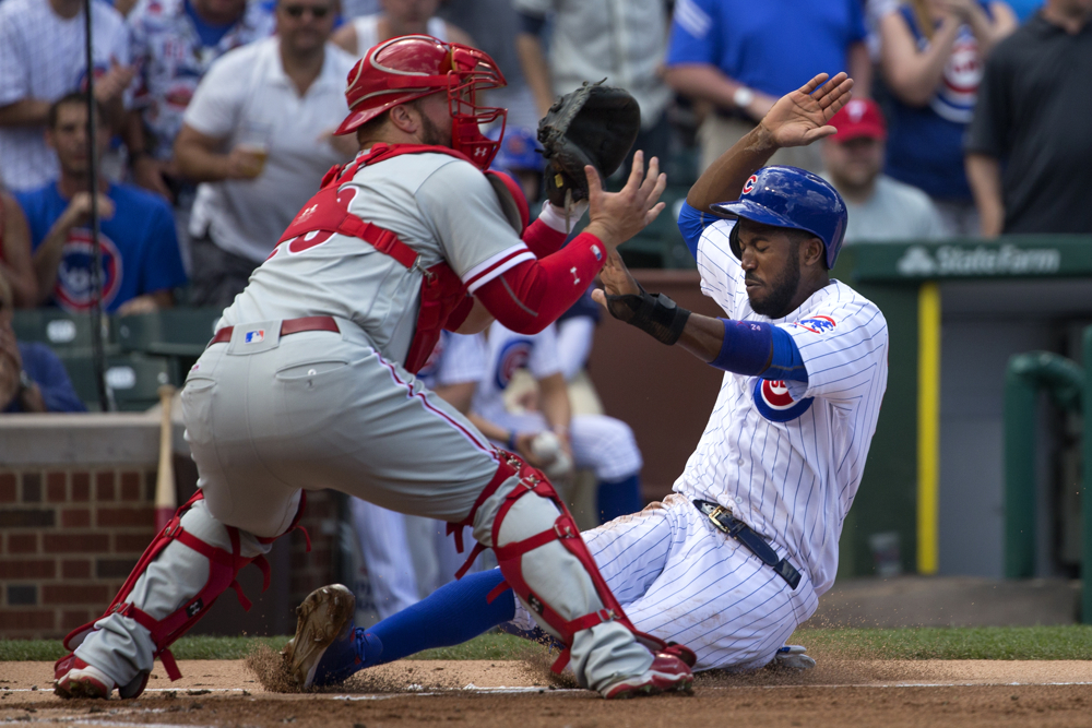 Chicago Cubs center fielder Dexter Fowler slides safely past Philadelphia Phillies catcher Cameron Rupp into home base on a hit from Chicago Cubs first baseman Anthony Rizzo during the first inning of the Chicago Cubs versus Philadelphia Phillies game at Wrigley Field Sunday, May 29, 2016, in Chicago. The Cubs won the game 7-2. (Erin Hooley/Chicago Tribune)