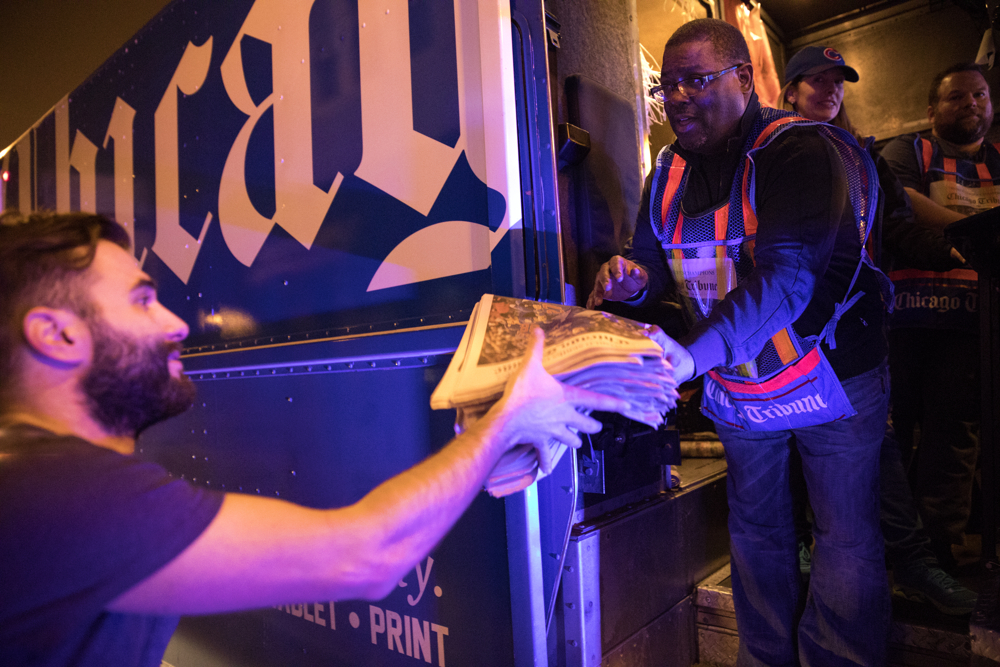 Michael Fanelli, left, buys a large stack of Chicago Tribune newspapers from 33-year employee Adirian Reed as fans celebrate the Chicago Cubs' historic World Series win over the Cleveland Indians Thursday, Nov. 3, in Wrigleyville in Chicago. (Erin Hooley/Chicago Tribune)