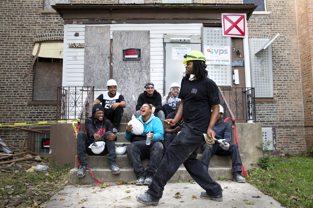 "Brendan Taylor dances as his coworkers, clockwise from top left, David Johnson, Dimitri Chavez, Vincent Glover, Kyline Puritt and Antonio Barr laugh at him as they take a break from deconstructing a house Wednesday, Oct. 12, 2016, in the Pullman neighborhood of Chicago. About 28 young men are participating in a pilot program launched by the Emerson Collective meant to help them learn job skills and find future employment while participating community renewal in many Chicago neighborhoods. One participant, Darius Fox, who was shot four times when he was 17 and spent several years in prison on a gun charge, said ""I like working a job. Just to have a job, that feels good, that help you feel better as a man…I ain't gotta look over my back, I ain't gotta watch out for the police, I ain't gotta worry about the police kicking in my door, nobody's trying to rob me. It's a blessing. I feel good. I feel like a man."" (Erin Hooley/Chicago Tribune)"