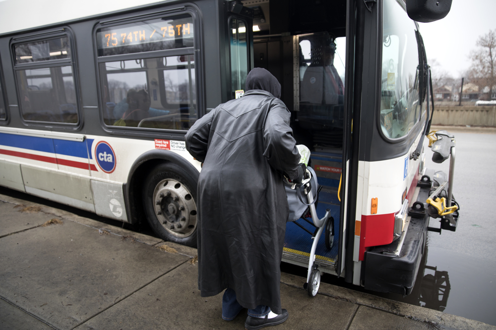 "71-year-old Kathyé Dawoudi boards a bus at the stop in the 7600 block of South State Street Tuesday, Jan. 3, 2017, in the Chatham neighborhood of Chicago. Dawoudi's 23-year-old grandson was shot and killed at his apartment building in 2015 about two blocks from the stop. ""I'm not going to let violence dictate me. For myself or any of my children,"" she said. (Erin Hooley/Chicago Tribune)"