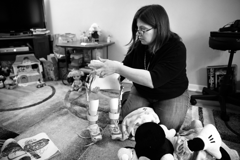 "Kimberly Dorencz-Cuervo, mother of 3-year-old Dayna Dorencz-Cuervo, adjusts her daughter's ankle-foot orthoses at her home Wednesday, Jan. 25, 2017, in the Morgan Park neighborhood of Chicago. Dorencz-Cuervo said her daughter uses the orthoses at home ""when she wants to."" (Erin Hooley/Chicago Tribune)"