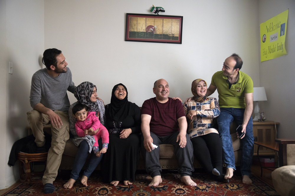 The Haj Khalaf family, who came to Chicago as Syrian refugees, from left, Mohamad, 22, Aya, 19, Sham, 19 months, matriarch Fattoum Bakir, patriarch Khaled Khalaf, Baraa, 23, and Abdulmajeed sit together at their home Friday, April 14, 2017, in Skokie, Ill. (Erin Hooley/Chicago Tribune)