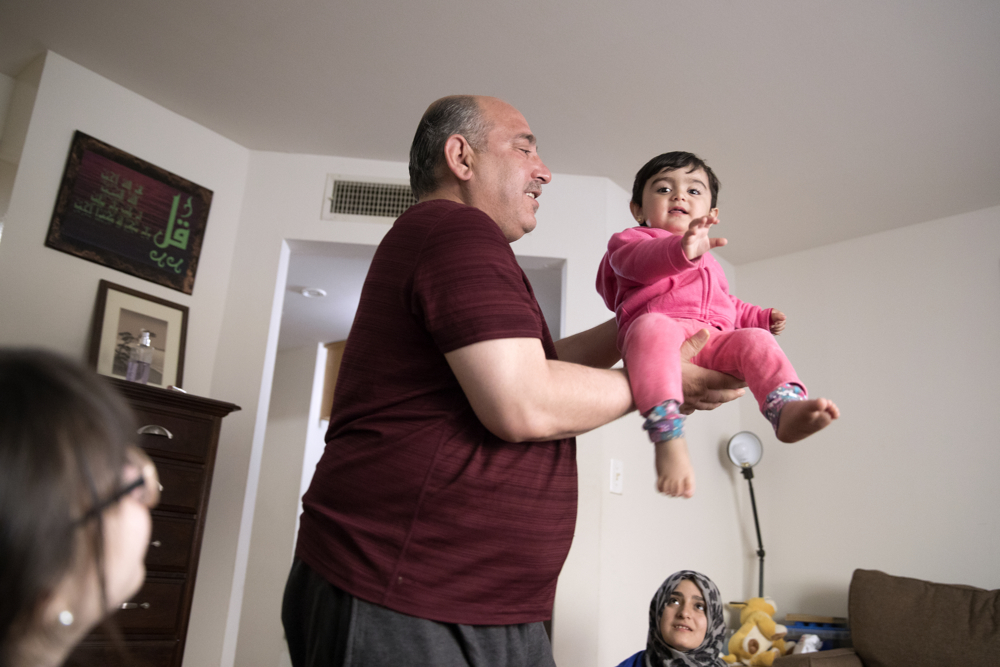 Syrian refugee Khaled Haj Khalaf holds up his 19-month-old granddaughter Sham at their home Friday, April 14, 2017, in Skokie, Ill. Fleeing the civil war in Syria, Haj Khalaf and his wife, Fattoum Bakir, came to Chicago in September 2016 with three of their children, but their oldest daughter Baraa Haj Khalaf, Sham's mother, and her family were denied entry in January of this year after President Donald Trump's immigration order banning all immigrants from Syria. Baraa, her husband Abdulmajeed and Sham spent two years in a Turkish refugee camp for the proper paperwork, interviews and background checks required to come to America. They were all finally reunited in February and now live together in the same apartment building. (Erin Hooley/Chicago Tribune)