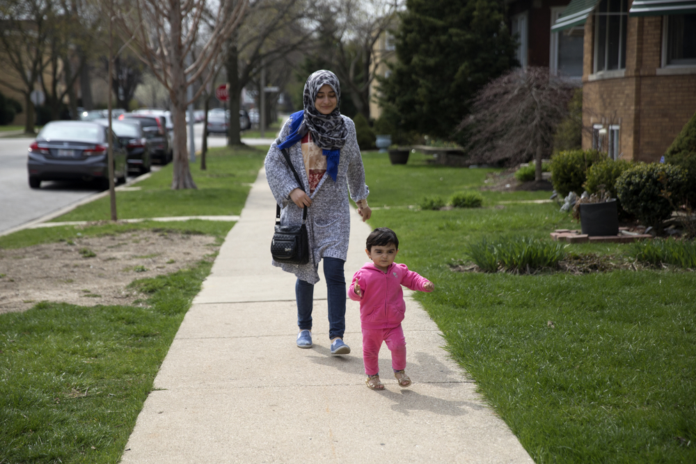 19-month-old Syrian refugee Sham Haj Khalad is followed by her 19-year-old aunt Aya Haj Khalad outside their home Friday, April 14, 2017, in Skokie, Ill. Fleeing the civil war in Syria, Sham's grandfather Khaled Haj Khalaf and his wife, Fattoum Bakir, came to Chicago in September 2016 with three of their children, but their oldest daughter Baraa Haj Khalaf and her family were denied entry in January of this year after President Donald Trump's immigration order banning all immigrants from Syria. Baraa, her husband Abdulmajeed and Sham spent two years in a Turkish refugee camp for the proper paperwork, interviews and background checks required to come to America. They were all finally reunited in February and now live together in the same apartment building. (Erin Hooley/Chicago Tribune)