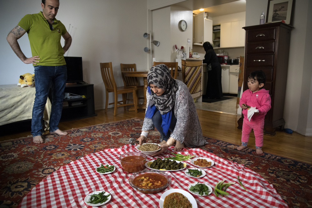 Aya Haj Khalaf, 19, puts put food as her family prepares to each lunch together at their home Friday, April 14, 2017, in Skokie, Ill. (Erin Hooley/Chicago Tribune)