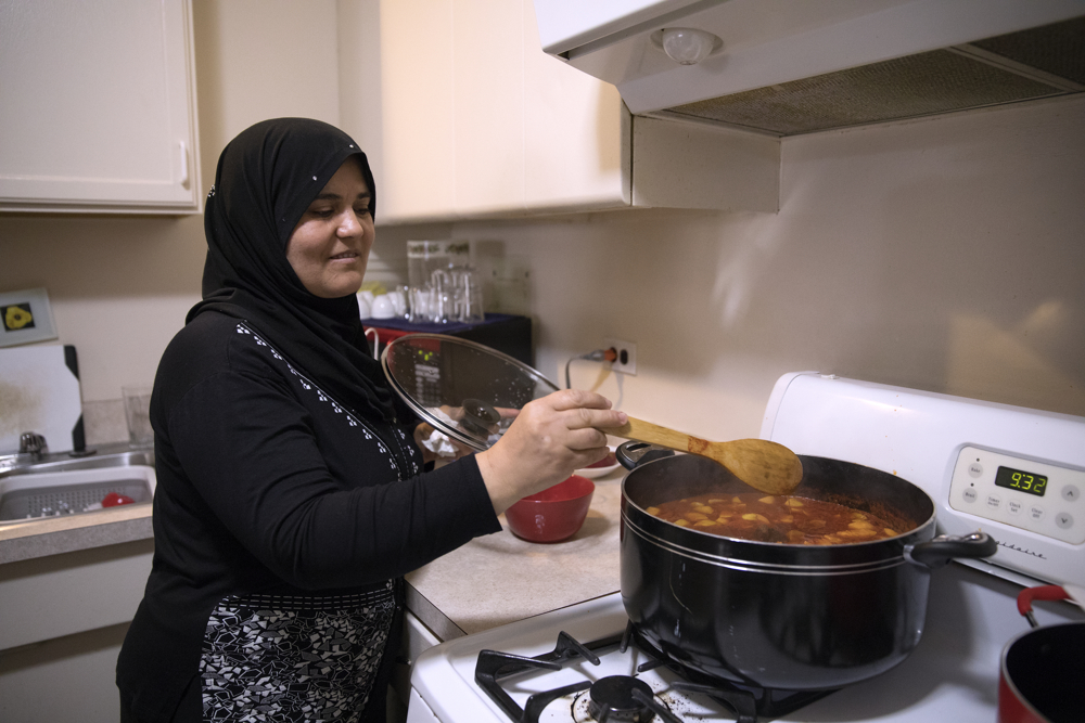 Syrian refugee Fattoum Bakir stirs food as she prepares lunch for her family at their home Friday, April 14, 2017, in Skokie, Ill. Fleeing the civil war in Syria, Bakir and her husband, Khaled Khalaf, came to Chicago in September 2016 with three of their children, but their oldest daughter Baraa Haj Khalaf and her family were denied entry in January of this year after President Donald Trump's immigration order banning all immigrants from Syria. Baraa, her husband Abdulmajeed and their now 19-month-old daughter Sham spent two years in a Turkish refugee camp for the proper paperwork, interviews and background checks required to come to America. They were all finally reunited in February and now live together in the same apartment building. (Erin Hooley/Chicago Tribune)