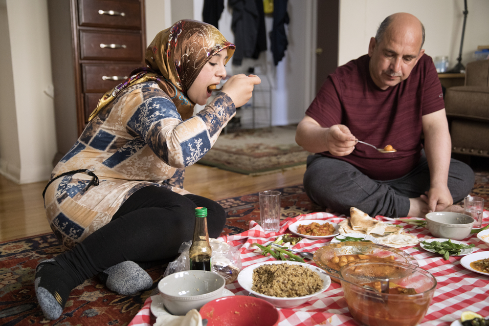 Baraa Haj Khalaf, left, eats lunch with her father Khaled Khalaf and their family at home Friday, April 14, 2017, in Skokie, Ill. (Erin Hooley/Chicago Tribune)