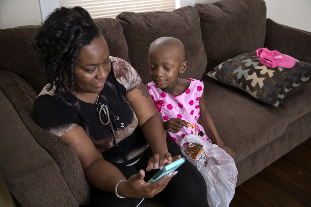 Tangela Watson shows photos to her daughter Jamela Anthony, 6, at their home Friday, July 7, 2017, in Chicago. Jamela has undergone extensive treatment for an aggressive tumor on her spinal cord that is now in remission. Her family has relied on Medicaid to cover costs. Watson worries about how the Medicaid program might change if the Senate's Obamacare replacement bill becomes law. (Erin Hooley/Chicago Tribune)