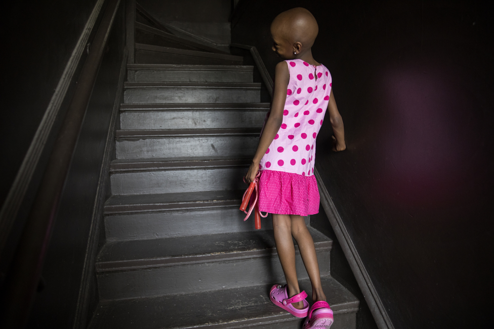 Jamela Anthony, 6, walks up the stairs to her home Friday, July 7, 2017, in Chicago. Jamela has undergone extensive treatment for an aggressive tumor on her spinal cord that is now in remission. Her family has relied on Medicaid to cover costs. Tangela Watson, Jamela's mother, worries about how the Medicaid program might change if the Senate's Obamacare replacement bill becomes law. (Erin Hooley/Chicago Tribune)