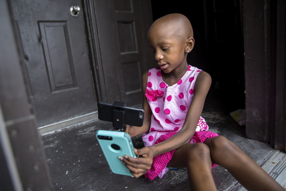 Jamela Anthony, 6, plays with two different phones at her home Friday, July 7, 2017, in Chicago. Jamela has undergone extensive treatment for an aggressive tumor on her spinal cord that is now in remission. Her family has relied on Medicaid to cover costs. Tangela Watson, Jamela's mother, worries about how the Medicaid program might change if the Senate's Obamacare replacement bill becomes law. (Erin Hooley/Chicago Tribune)