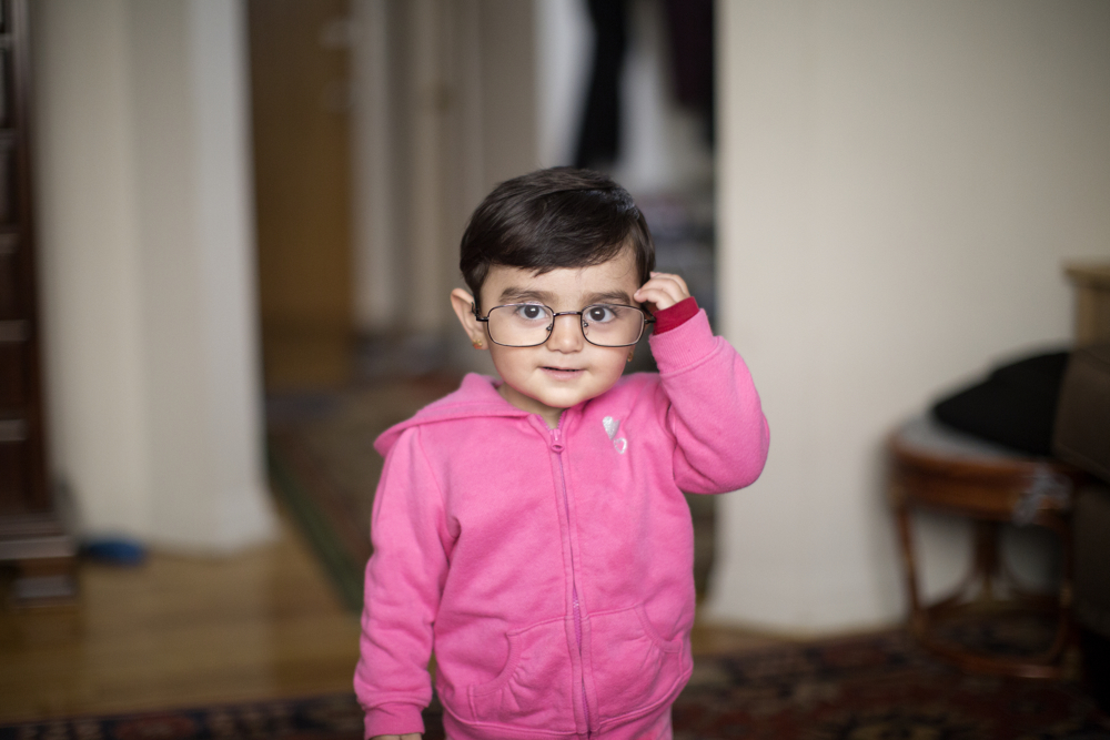 19-month-old Syrian refugee Sham Haj Khalad wears her grandfather's glasses at her home Friday, April 14, 2017, in Skokie, Ill. Fleeing the civil war in Syria, Sham's grandfather Khaled Haj Khalaf and his wife, Fattoum Bakir, came to Chicago in September 2016 with three of their children, but their oldest daughter Baraa Haj Khalaf and her family were denied entry in January of this year after President Donald Trump's immigration order banning all immigrants from Syria. Baraa, her husband Abdulmajeed and Sham spent two years in a Turkish refugee camp for the proper paperwork, interviews and background checks required to come to America. They were all finally reunited in February and now live together in the same apartment building. (Erin Hooley/Chicago Tribune)
