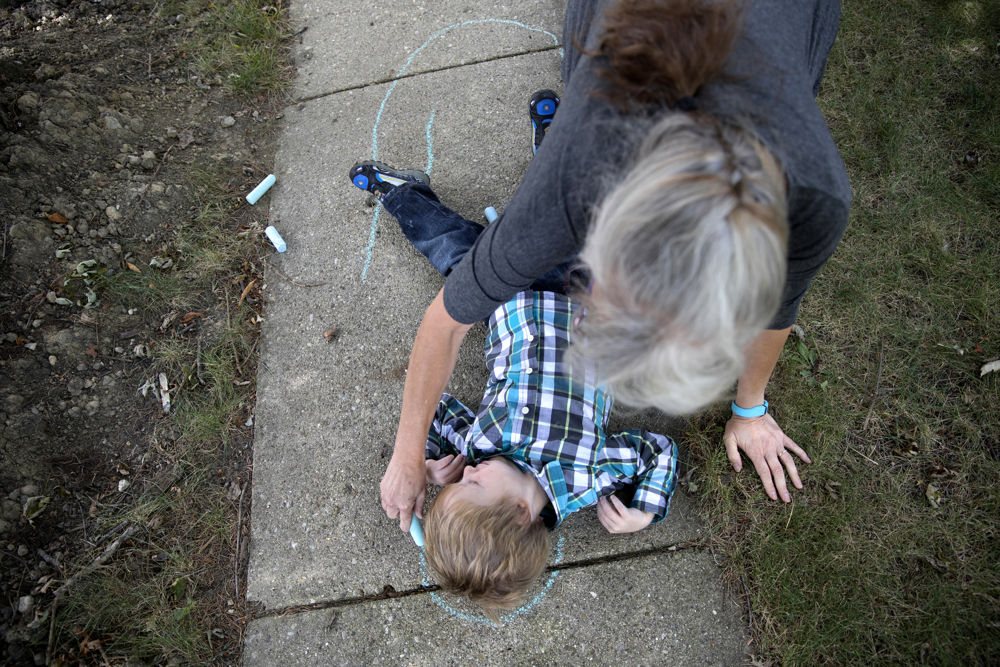 Lorraine Szontagh draws around her grandson Marshall Szontagh, 3, with sidewalk chalk Wednesday, Sept. 6, 2017, at her house in Elmwood Park, Ill. Marshall and his brother Jackson, 4, were poisoned by lead paint while their family lived in a three flat in Berwyn. Caitlin, the children's mother, said they have already developed some behavioral problems and learning disabilities but it may take years to find out the full extent of their injuries from the poisoning. (Erin Hooley/Chicago Tribune)
