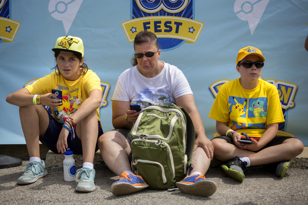 From left, Alison Richards, 13, Diedra Richards and Alex Richards, 10, sit on the ground as they struggle to play Pokemon Go at the Pokemon Go Fest Saturday, July 22, 2017, at Grant Park in Chicago. Many festival attendees had trouble getting the augmented-reality cellphone game to work. By the afternoon, Mike Quigley, chief marketing officer of the game's developer, Niantic, announced all ticket holders would receive refunds and be issued $100 in credits for use in the app. (Erin Hooley/Chicago Tribune)