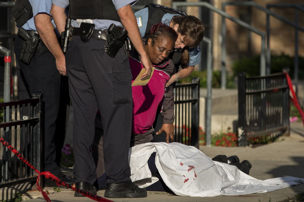 "The mother of Kennatay Leavell kneels over his body outside a group of row houses in the 500 block of West Iowa Street Friday, July 28, 2017, in the Cabrini Green neighborhood of Chicago. The 31-year-old was shot multiple times in the face and died at the scene. Family members had been watching for an hour, held back from Leavell's then-uncovered body by police tape and officers, when his mother eventually found a way through one of the Cabrini Green apartments. ""My baby,"" she cried as she struggled to hold him close to her. ""My baby."" (Erin Hooley/Chicago Tribune)"