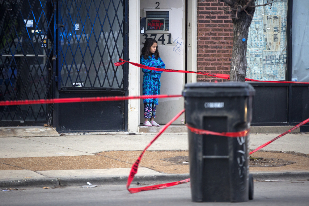 A young girl stands in the doorway of an apartment near the scene of a fatal shooting in the 3700 block of West Fullerton Avenue Friday, Feb. 3, 2017, in the Logan Square neighborhood of Chicago. One 20-year-old man, the driver of a white vehicle stopped outside a cafe in the area, was shot in the hand and treated at Norwegian American Hospital while his co-worker and passenger, also in his 20s, was shot in the head and neck and died at the scene. (Erin Hooley/Chicago Tribune)