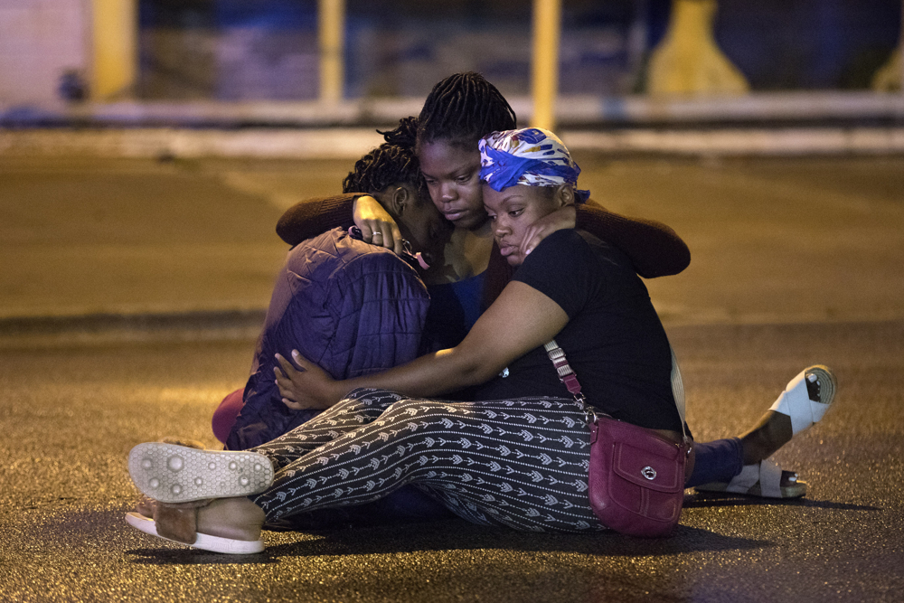 Three women hold each other as they sit on the ground at the scene of a fatal double shooting in the 5400 block of South Wabash Avenue Thursday, June 29, 2017, in the Washington Park neighborhood of Chicago. 32-year-old Jeanine Dowell and 41-year-old Juliet Washington were driving north when shots were fired from another vehicle, striking both women in the head. They were pronounced dead at the scene. (Erin Hooley/Chicago Tribune)
