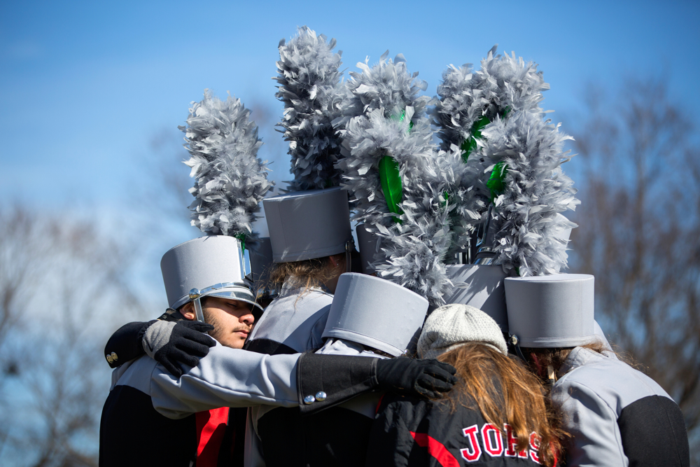 Jose Moreno, left, 17, huddles together with other members of the John Overton High School of Nashville marching band as they wait in the cold for their turn to join the St. Patrick's Day Parade Saturday, March 11, 2017, in Chicago. (Erin Hooley/Chicago Tribune)