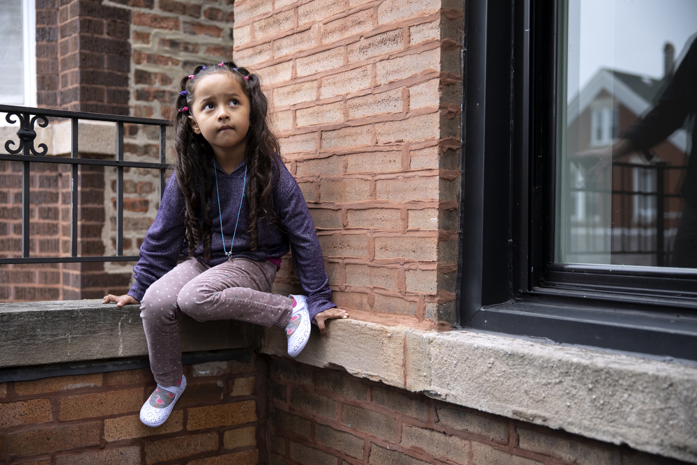 Skarleth Fernandez Flores, 6, sits on a balcony at the home of the DeMay-Gres family, who is sponsoring her family as they seek asylum status in the United States, Sunday, May 20, 2018, in Chicago. The family left their home country of El Salvador years ago due to gang violence, living in Guatemala for awhile before ending up in Mexico. They crossed the border into the United States as part of a caravan of hundreds of people, organized by Pueblo Sin Frontreras, where they surrendered and sought asylum. Pueblo Sin Frontreras worked with Showing Up for Racial Justice, a national network of activists, to find sponsor families to house those in the caravan who did not have relatives in the United States. (Erin Hooley/Chicago Tribune)