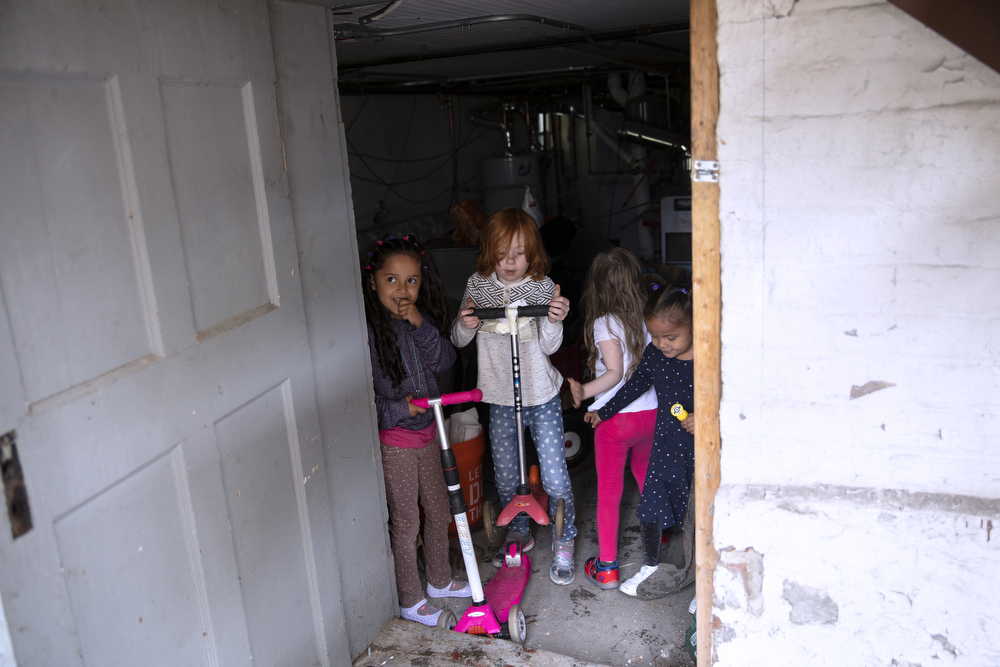 From left, Skarleth Fernandez Flores, 6, Anthony DeMay-Gres, 6, Maggie DeMay-Gres, 4, and Perla Flores Delgado, 3, retrieve scooters from the basement of the DeMay-Gres family, who is sponsoring the Flores family as they seek asylum status in the United States, Sunday, May 20, 2018, in Chicago. The family left their home country of El Salvador years ago due to gang violence, living in Guatemala for awhile before ending up in Mexico. They crossed the border into the United States as part of a caravan of hundreds of people, organized by Pueblo Sin Frontreras, where they surrendered and sought asylum. Pueblo Sin Frontreras worked with Showing Up for Racial Justice, a national network of activists, to find sponsor families to house those in the caravan who did not have relatives in the United States. (Erin Hooley/Chicago Tribune)