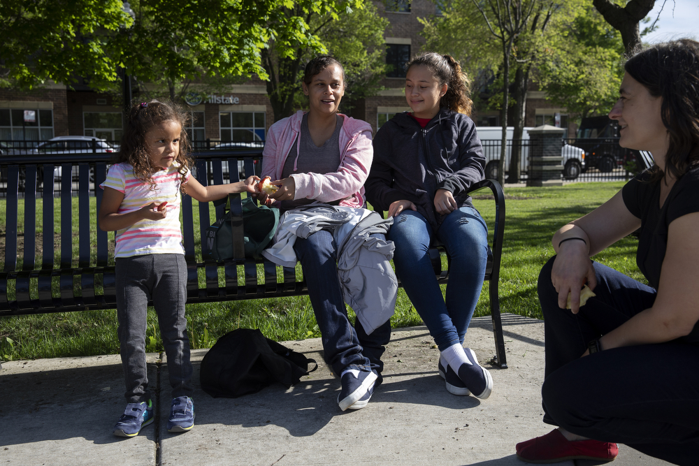 Maritza Flores, center, with her daughters Perla Flores Delgado, 3, left, and Mariana Portillo Flores, 16, speak with Liz Gres, right, at Dunbar Park Wednesday, May 23, 2018, in Chicago. The Flores family left their home country of El Salvador years ago due to gang violence, living in Guatemala for awhile before ending up in Mexico. They crossed the border into the United States as part of a caravan of hundreds of people, organized by Pueblo Sin Frontreras, where they surrendered and sought asylum. Pueblo Sin Frontreras worked with Showing Up for Racial Justice, a national network of activists, to find sponsor families, like the DeMay-Gres family in Chicago, to house those in the caravan who did not have relatives in the United States. (Erin Hooley/Chicago Tribune)